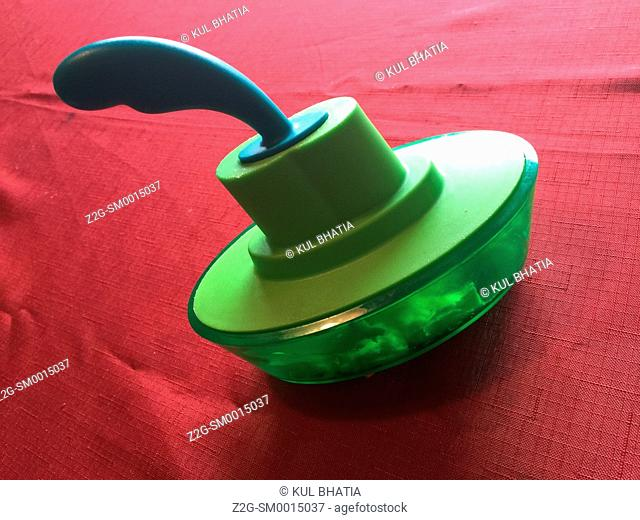 A green butter dish shaped like a boat on red table cloth, Ontario, Canada