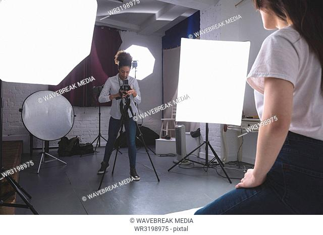 Female photographer clicking photos of model