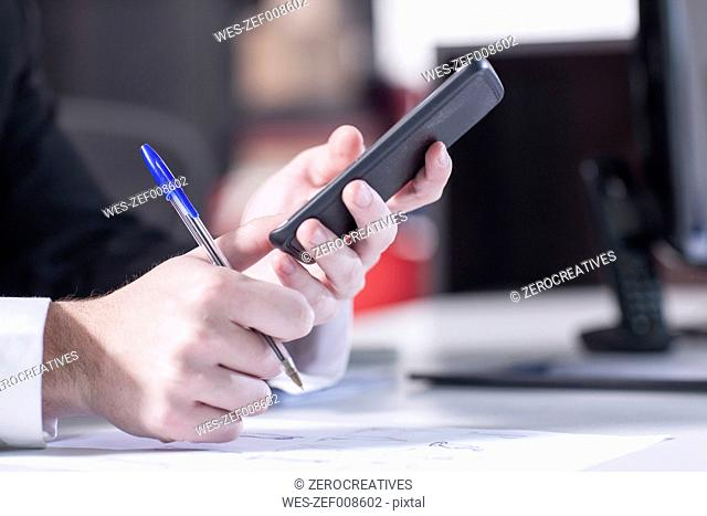 Hands of businessman holding smart phone and ball pen