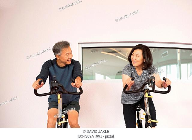Front view of mature couple using exercise bikes face to face smiling