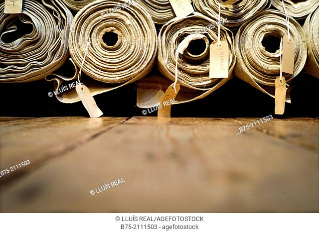 a lot of fabric rolls in a warehouse, with a description and a price per meter in London, England, UK, Europe