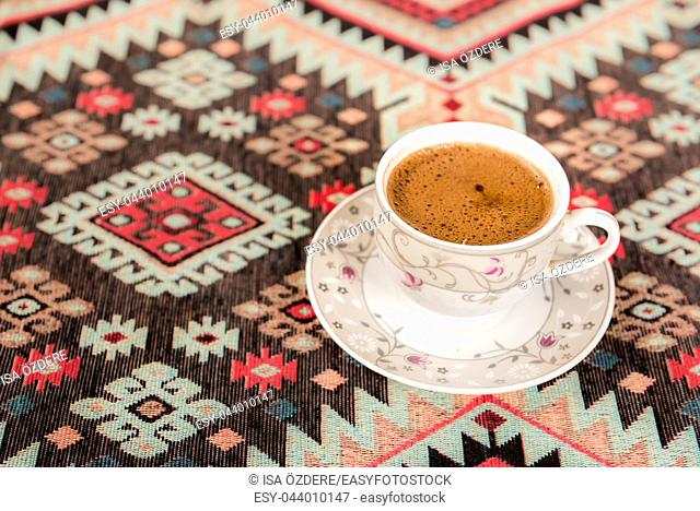 Top view of Traditional Turkish coffee cooked on embers is served in a cup on a traditional Turkish rug