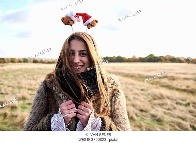 Portrait of happy young woman wearing Christmassy headdress in the countryside