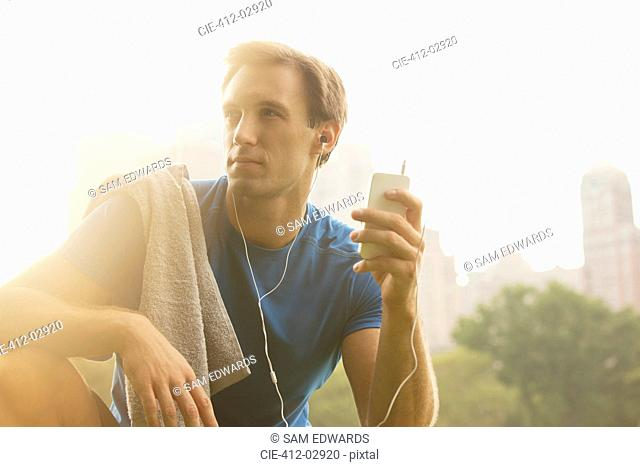Runner listening to mp3 player in park