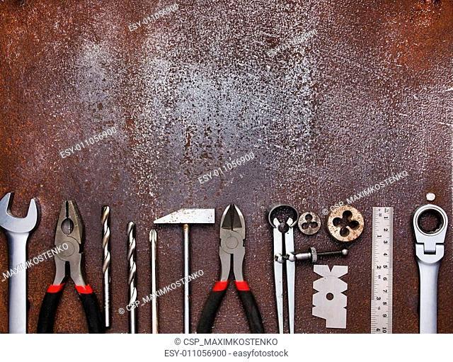 Metal workshop tools on old metal background