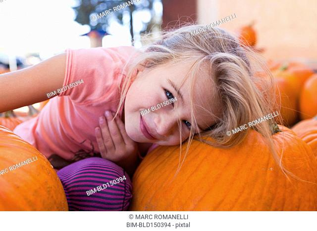 Caucasian girl sitting with pumpkins