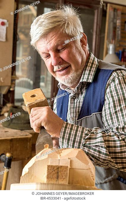 Wooden mask carver using wood carving tools on a wooden block, wooden mask, Bad Aussee, Styria, Austria