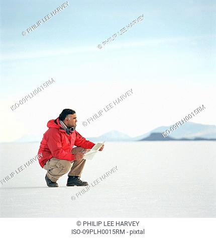 Man crouching in the desert looking