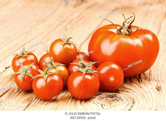 whole and crushed tomatoes on wooden board