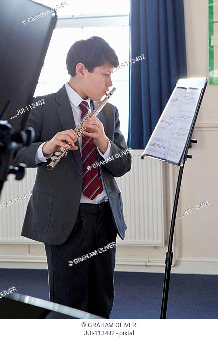 Middle school student playing flute with sheet music in music class