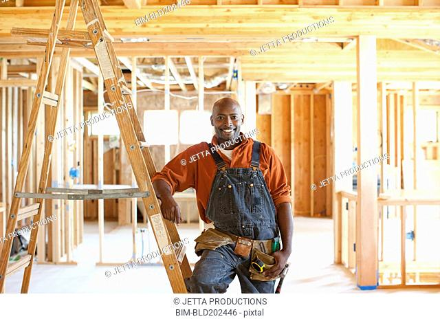 Black construction worker standing in unfinished room