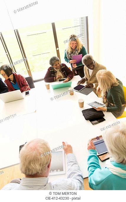 Senior business people using digital tablets and laptops in conference room meeting