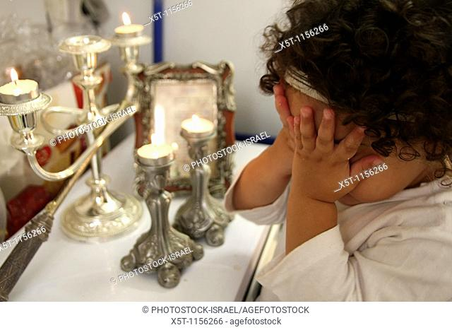 Young Jewish girl of five lights the traditional Shabbat Sabbath candles on Friday night