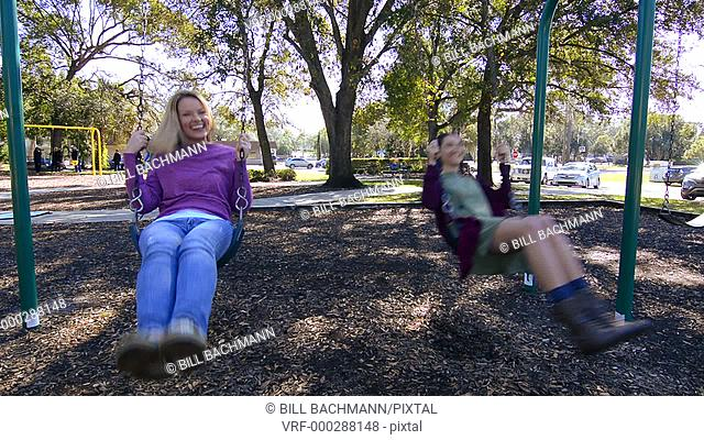 Mother and daughter swinging on swings in the park having fun with laughter and love, Model released MR-2, MR-6