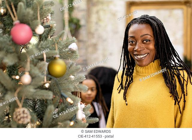 Portrait smiling, confident woman at Christmas tree