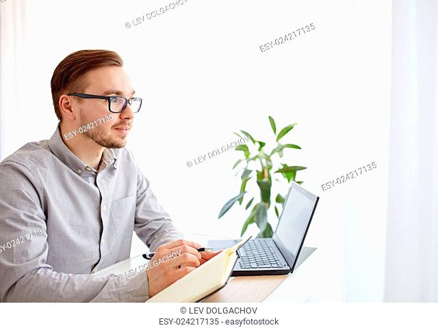 business, startup, inspiration and people concept - happy businessman or creative male worker with notebook or diary thinking at home office