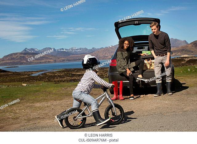 Parents watching son ride bike, Loch Eishort, Isle of Skye, Hebrides, Scotland