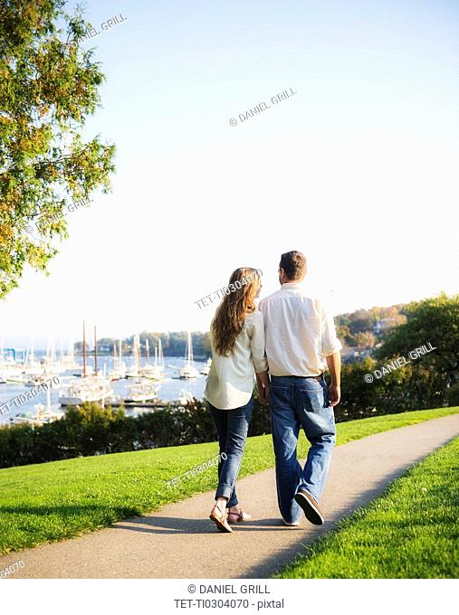 Couple walking with harbor in background