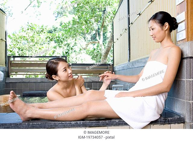 Naked young woman with towel at hot spring talking