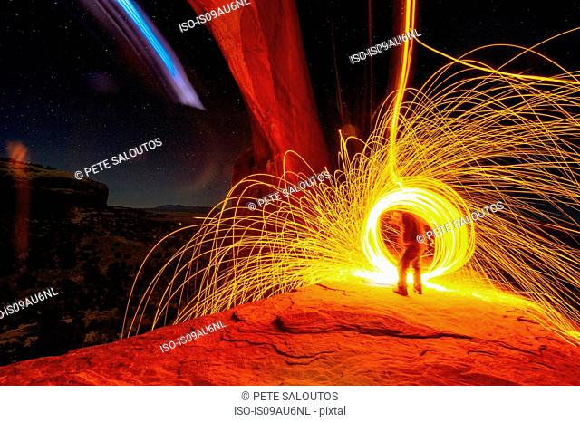 Mature man creating long exposure light painting on cliff side, Moab, Utah, USA