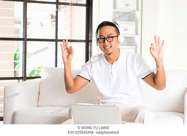Handsome Asian man using tablet computer. Smiling Southeast Asian college student relaxing and listening to music at home. Asian model..