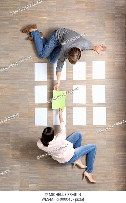 Businessman and businesswoman sitting on floor organizing blank sheets of paper