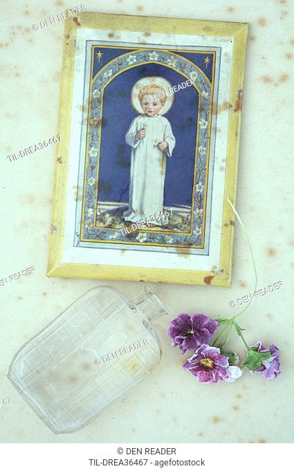 Vintage print of angelic child with halo lying on antique paper with old perfume bottle and dried mauve Pelargonium flowers