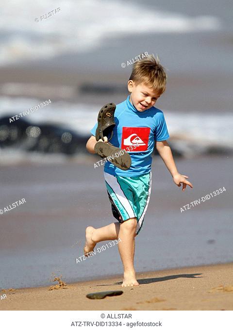 YOUNG BOY WALKS OUT OF SEA; BALLITO, DOLPHIN COAST, SOUTH AFRICA; 09/07/2010