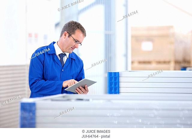 Supervisor worker stock checking solar panels in factory warehouse