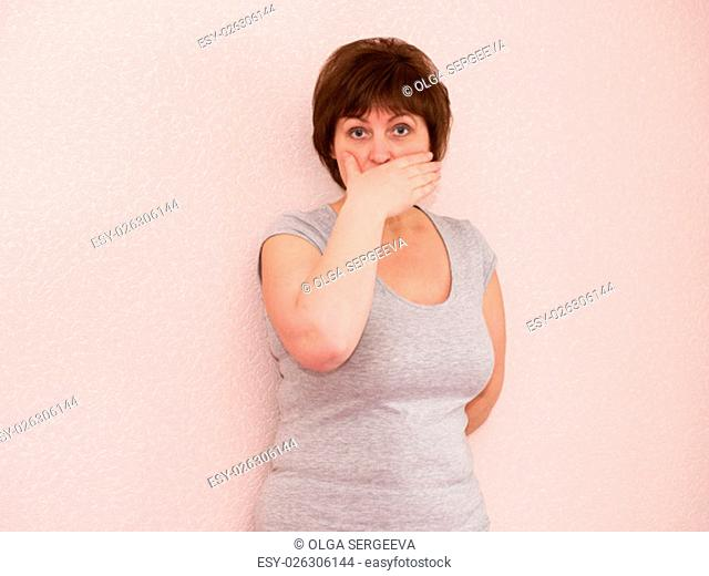 Portrait attractive mature woman with shocked, surprised, anxious facial expression, covering mouth with hand on plain background