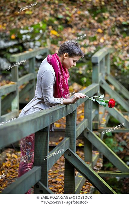 Lonesome young lady with rose flower in hand