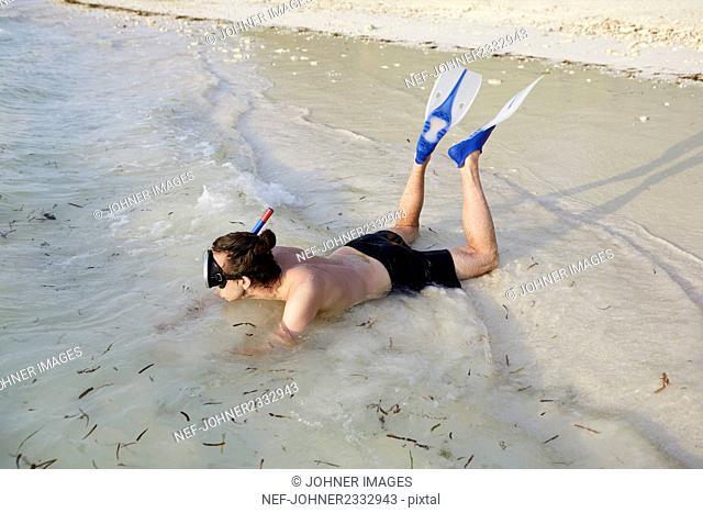 Man on beach with scuba mask