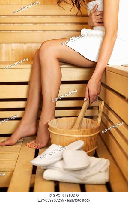 Woman relaxing and using sauna accessories