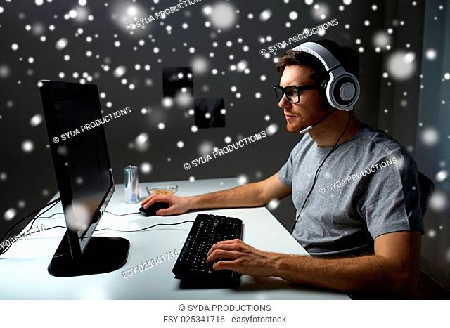technology, gaming, entertainment, let's play and people concept - young man in headset and glasses with pc computer playing game at home and streaming...