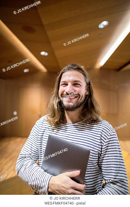 Portrait of laughing man with laptop in university