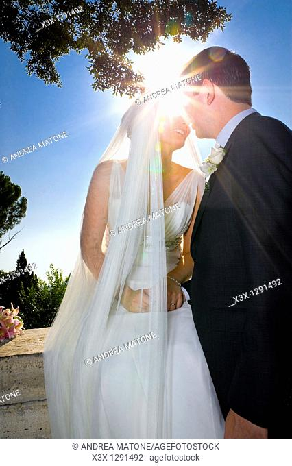 Newlyweds kissing against the sun