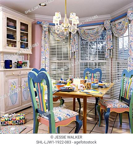EATING AREA: Near kitchen. Pastel painted chairs, birthday party, table setting, chandelier, swag and jabot curtains with blinds, crown molding