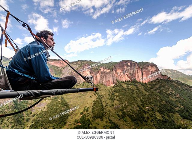 Rock climber sitting on portaledge, looking at view, Liming, Yunnan Province, China