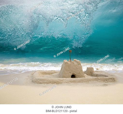 Wave crashing toward sand castle on beach