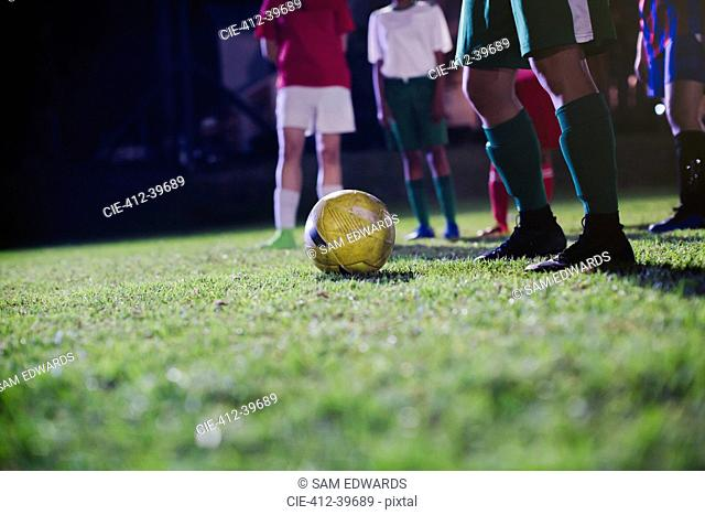 Young female soccer players practicing on field at night