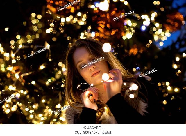 Young woman looking at lights in her hand, tree in background