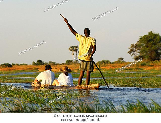 Punter with tourists in the traditional Mokoro dugout canoes on excursion in the Okavango Delta, Botswana, Africa