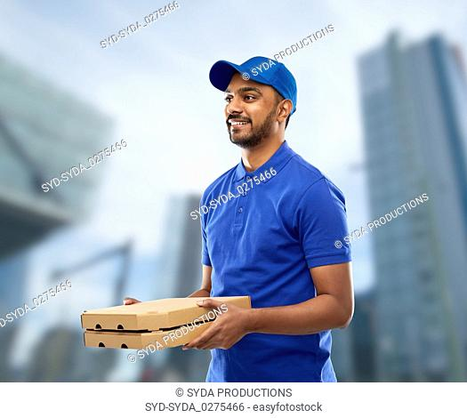 happy indian delivery man with pizza boxes in blue