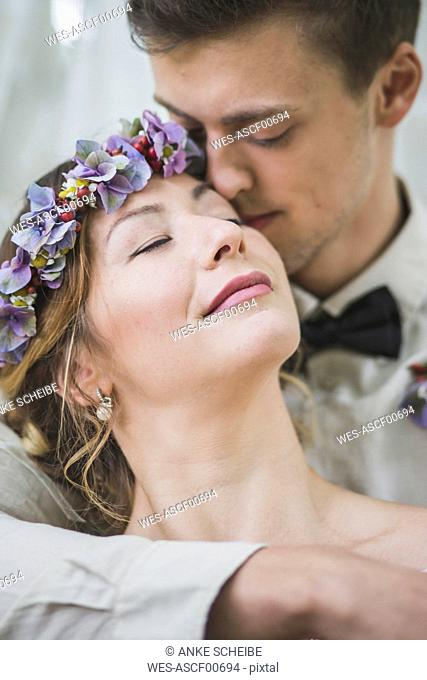Close-up of bride and groom embracing