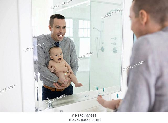 Father holding surprised baby son at bathroom mirror