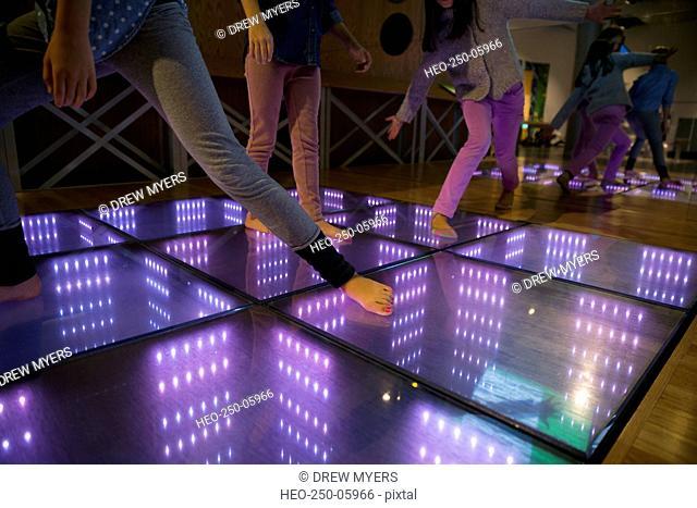 Barefoot girls dancing illuminated floor science center exhibit
