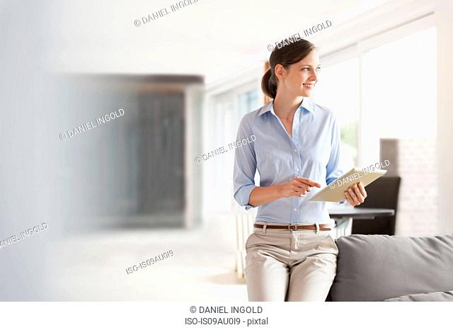Woman using digital tablet to control home automation system in living room