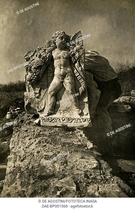 Marble relief depicting an eros holding a garland with a bunch of grapes, archaeological site of Ostia Antica, Lazio, Italy, ca 1910