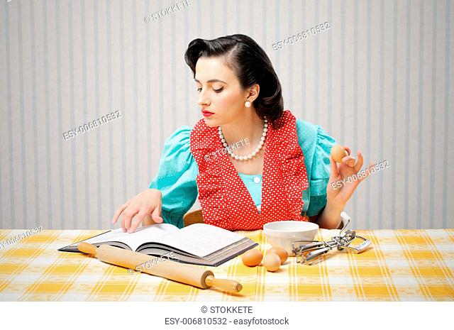 Young woman looking at a Recipe for a cake
