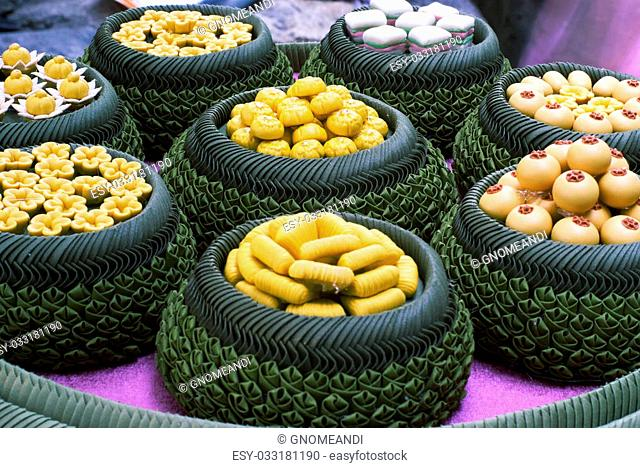 A variety of Thai desserts arranged nicely in bowls made from banana leaves